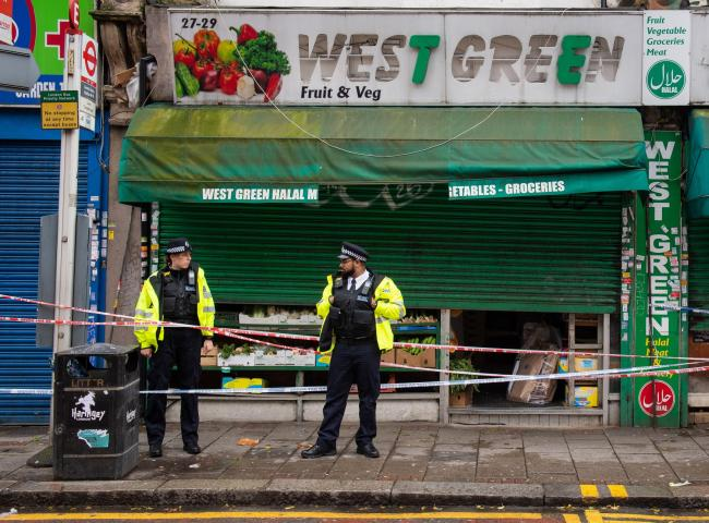 Police outside the butchers in West Green Road Credit: PA