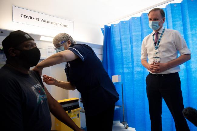 Chief Executive of the National Health Service in England, Sir Simon Stevens, watches on as a person receives their vaccination. Photo: PA
