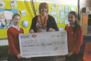 Pupils hand over their cheque to NSPCC representative Ginny Donnelly
