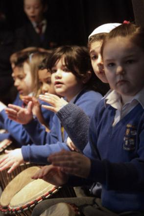 Pupils perform using West African drums known as djembe