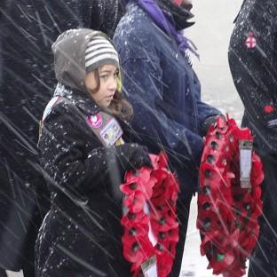 A girl holds a wreath at the Liberation Memorial in Stanley to mark the 30th anniversary of the liberation of the Falkland Islands