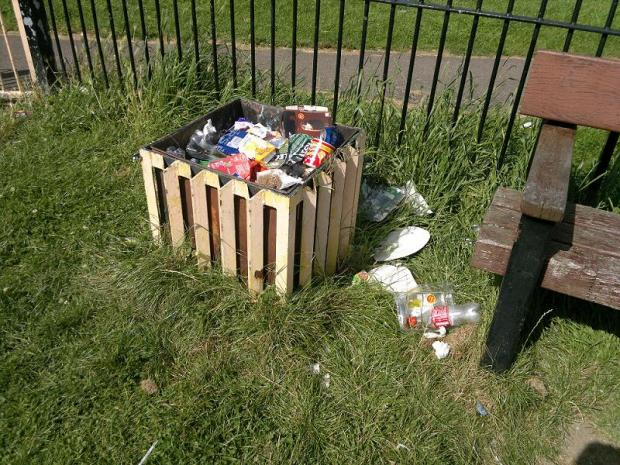 Rubbish overflows from the open bin