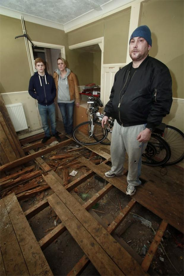 James Perry, Amanda Eaton and Dean Perry in thr wreckage of their living room