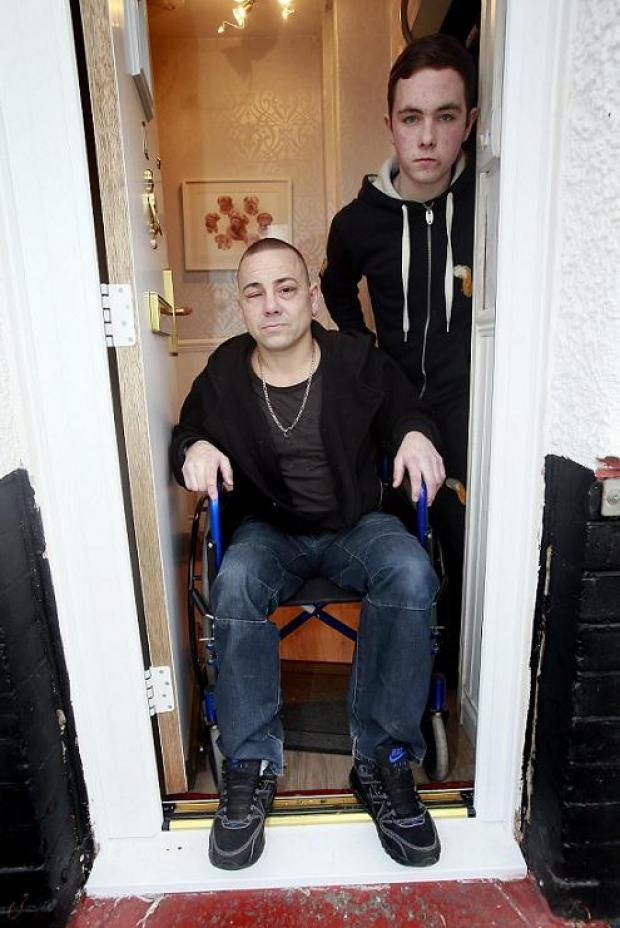 Paul Davies and his son Jay by their front door which does not allow wheelchair access